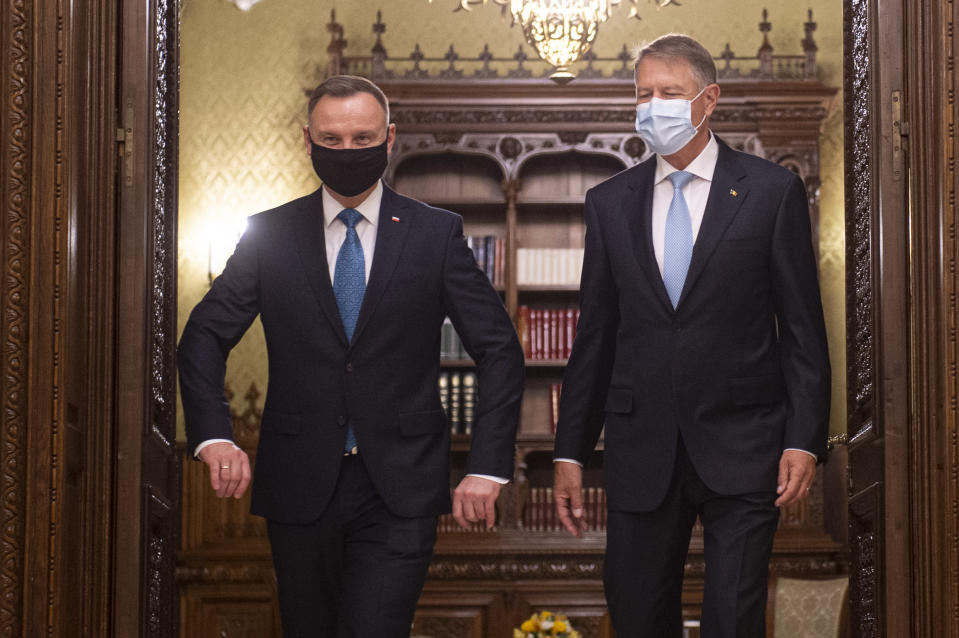Polish President Andrzej Duda, left, walks with Romanian President Klaus Iohannis at the Cotroceni presidential palace in Bucharest, Romania, Monday, May 10, 2021. (AP Photo/Alexandru Dobre)