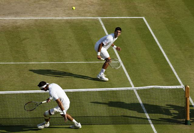 Serbia's Novak Djokovic (top) in action with Argentina's Juan Martin Del Potro after his win during day eleven of the Wimbledon Championships at The All England Lawn Tennis and Croquet Club, Wimbledon.
