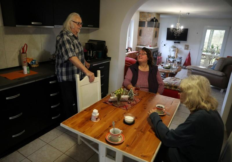 Waldemar Hackstaetter and his wife Hildegard chat with their neighbour Brigitte Haager-Horn in their house in the village of Sirakovo