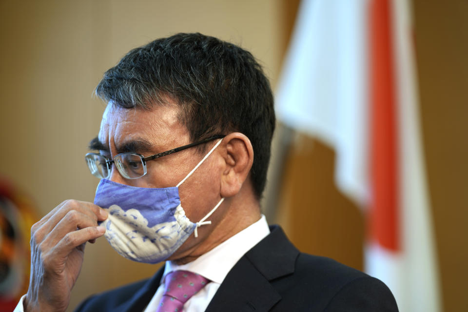 Taro Kono, Japan's minister in charge of a huge vaccination campaign, adjusts his face mask during an interview with The Associated Press at his office in Tokyo Wednesday, July 28, 2021. As Olympics host Tokyo saw another record number of coronavirus cases Wednesday, Kono told that the speed of the inoculation campaign, which is averaging about 10 million shots a week after a late start, is less urgent than getting shots to young people, who are blamed for spreading the virus. (AP Photo/Eugene Hoshiko)