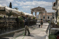 FILE - In this Saturday, May 23, 2020 file photo, a man sprays water at umbrellas outside a tavern at Plaka district, in Athens, as the restaurant prepares for reopening. Greece's Prime Minister Kyriakos Mitsotakis said Wednesday April 21, 2021, the country's tourism industry will open on May 15 when a ban on travel between different regions in the country will be lifted, adding that restaurants and cafes will also be allowed to reopen outdoor areas starting on May 3. (AP Photo/Yorgos Karahalis, File)