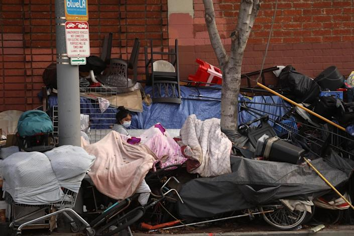 A woman's head and shoulders are visible as she walks between piles of belongings at a sidewalk homeless camp