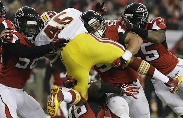 Washington Redskins running back Alfred Morris (46) is stopped by Atlanta Falcons outside linebacker Paul Worrilow (55) and other Atlanta Falcons team mates during the first half of an NFL football game, Sunday, Dec. 15, 2013, in Atlanta. (AP Photo/David Goldman)