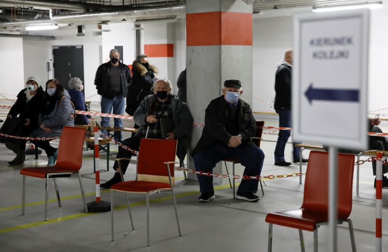 FILE PHOTO: People wearing protective masks wait in line at the coronavirus disease (COVID-19) vaccine centre situated at a temporary hospital organised at the National Stadium in Warsaw