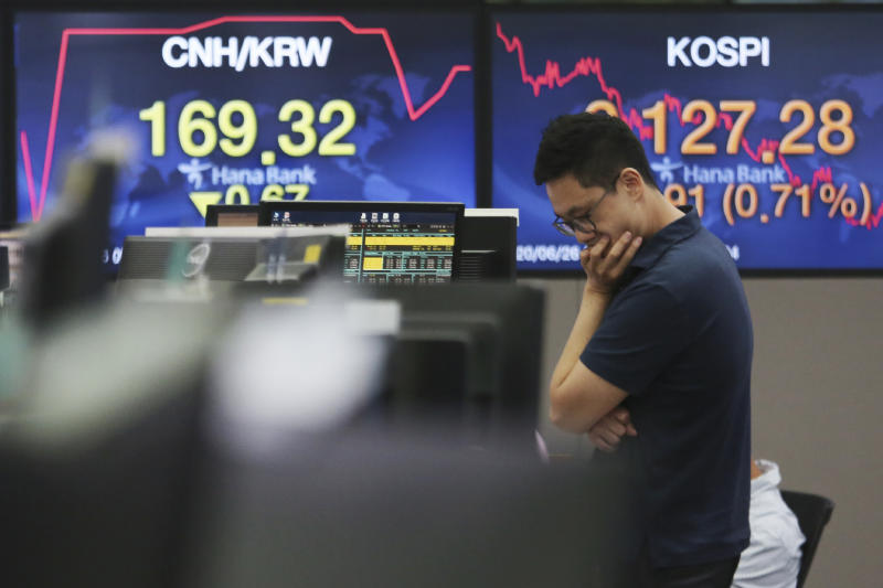 A currency trader works at the foreign exchange dealing room of the KEB Hana Bank headquarters in Seoul, South Korea, Friday, June 26, 2020. Asian stock markets followed Wall Street higher on Friday after U.S. regulators removed some limits on banks' ability to make investments. (AP Photo/Ahn Young-joon)