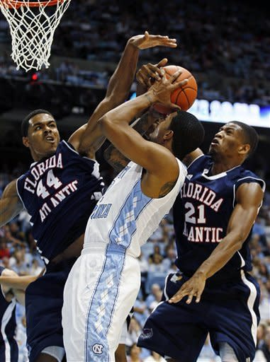 North Carolina's Leslie McDonald, center, tries to shoot as Florida Atlantic's Kelvin Penn (44) and Jordan McCoy (21) defend during the first half of an NCAA college basketball game in Chapel Hill, N.C., Sunday, Nov. 11, 2012. (AP Photo/Gerry Broome)