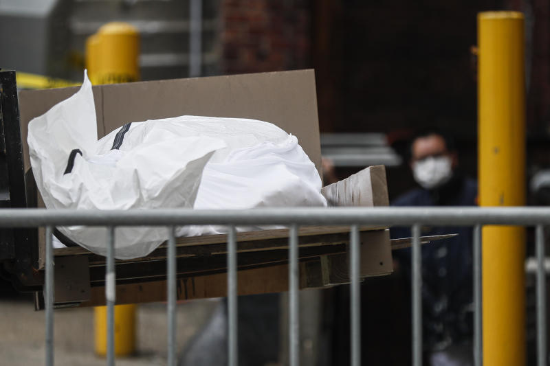 A body wrapped in plastic is loaded onto a refrigerated container truck used as a temporary morgue by medical workers due to COVID-19 concerns, Tuesday, March 31, 2020, at Brooklyn Hospital Center in the Brooklyn borough of New York. The new coronavirus causes mild or moderate symptoms for most people, but for some, especially older adults and people with existing health problems, it can cause more severe illness or death. (AP Photo/John Minchillo)
