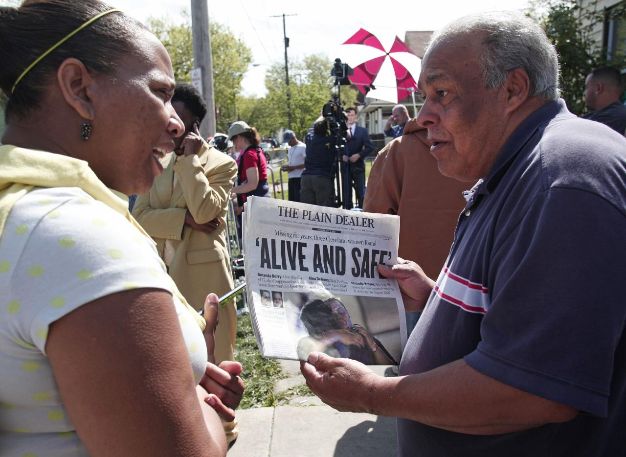CLEVELAND, OH - MAY 7:  A man shows page one of The Plain Dealer newspaper to a friend while people gather along Seymour Avenue near the house where three women, who disappeared as teens about a decade ago, were found alive, May 7, 2013 in Cleveland, Ohio. Amanda Berry, who went missing in 2003, Gina DeJesus, who went missing in 2004, and Michelle Knight, who went missing in 2002, managed to escape their captors on May 6, 2013. Three suspects, all brothers, were taken into custody.   (Photo by Bill Pugliano/Getty Images)
