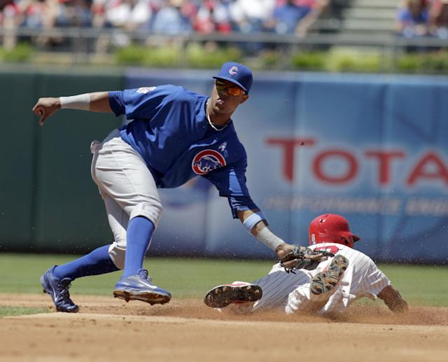 Chicago Cubs' Starlin Castro, left, moves for a late tag as Philadelphia Phillies' Ben Revere steals second in the first inning of a baseball game on Sunday, June 15, 2014, in Philadelphia. (AP Photo/H. Rumph Jr)