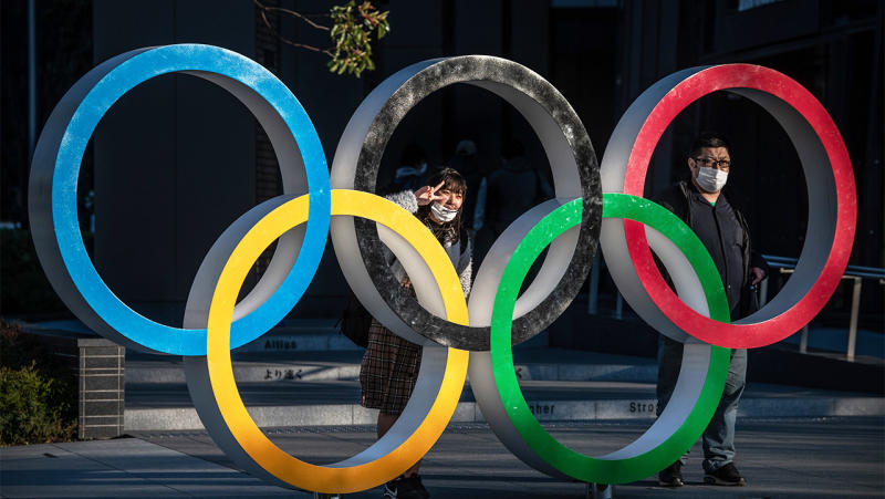 People wearing face masks pose for photographs next to Olympic Rings in Japan.