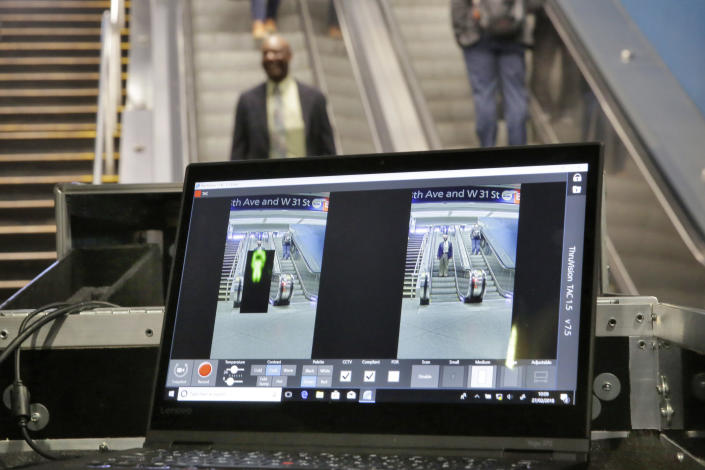 FILE - In this Tuesday, Feb. 27, 2018 file photo ThruVision suicide vest-detection technology reveals a suspicious object on a man, at left, during a Transportation Security Administration demonstration in New York's Penn Station. Los Angeles is poised to have the first mass transit system in the U.S. with body scanners that screen passengers for weapons and explosives. Officials from the Los Angeles County Metropolitan Transportation Authority and the Transportation Security Administration have scheduled a Tuesday, Aug. 14, 2018, news conference. The TSA has been working on the experimental devices, known as standoff explosive detection units, since 2004 with transit agencies. They hadn't been deployed permanently at any transit hub. (AP Photo/Richard Drew,File)