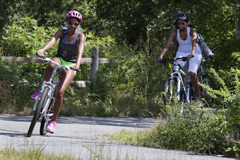 Sasha Obama, left, followed by her mother, first lady Michelle Obama, ride their bikes in Manuel F. Correllus State Forest in West Tisbury, Mass., Friday, Aug. 16, 2013, during their family vacation on the island of Martha's Vineyard. President Barack Obama, with daughter Malia, rode by shortly after. (AP Photo/Jacquelyn Martin)