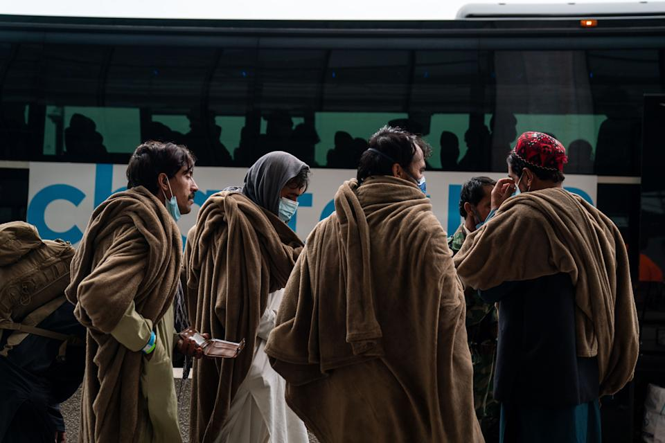 Evacuees who fled Afghanistan walk through the terminal to board buses that will take them to a processing center, at Dulles International Airport on Tuesday, Aug. 31, 2021. (Kent Nishimura / Los Angeles Times via Getty Images)