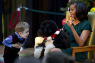 FILE - In this Dec. 14, 2012, file photo A.J. Murray, left, peeks in close at first dog Bo, as first lady Michelle Obama, answers questions from children who are patients at the Children's National Medical Center in Washington. Former President Barack Obama's dog, Bo, died Saturday, May 8, 2021, after a battle with cancer, the Obamas said on social media. (AP Photo/Jacquelyn Martin, File)
