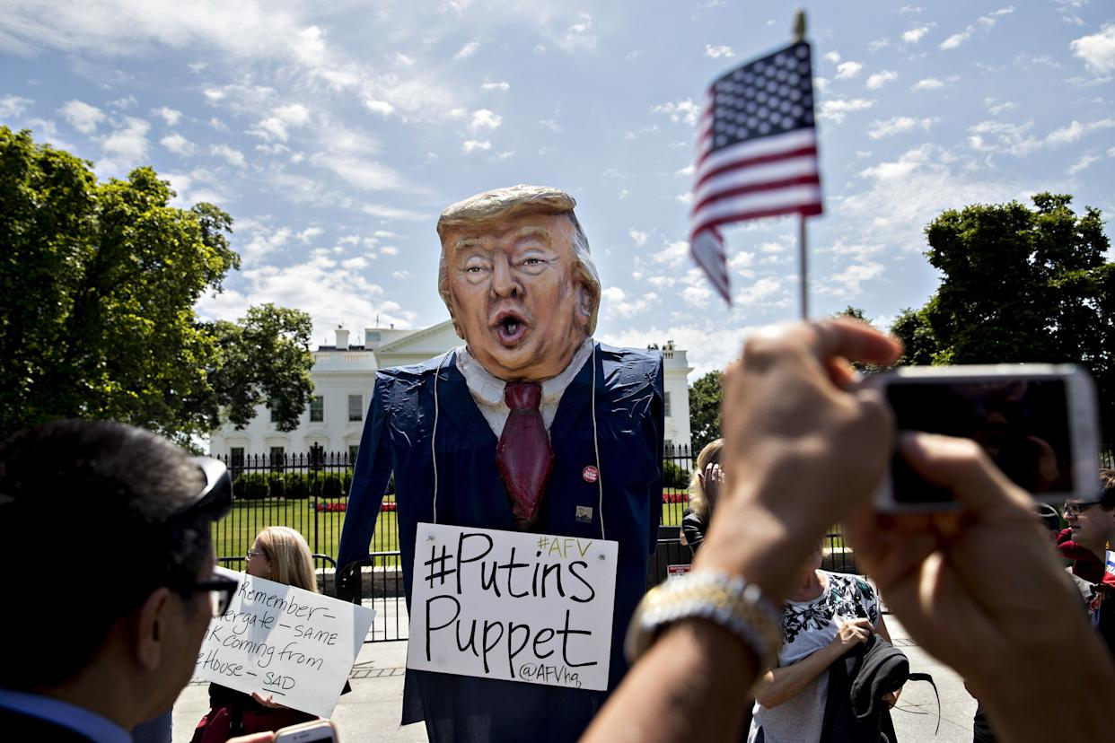 """A demonstrator wears an effigy of President Donald Trump with a sign that reads """"Putins Puppet"""" during a protest outside the White House on May 10. Russian Foreign Minister Sergei Lavrov arrived at the White House that dayfor a meeting with Trump, the day after the president fired the FBI director who had been leading an investigation into possible Trump campaign collusion with Russian officials."""