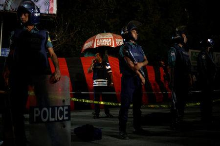 A security personnel talks over a walky-talky while others stand guard in front of the spot where a suicide bomber blew himself up near the Shahjalal International Airport in Dhaka