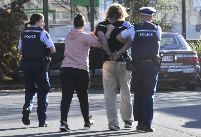 Police take a suspect into custody near the Countdown supermarket in central Dunedin, New Zealand, Monday, May 10, 2021. A man began stabbing people at a New Zealand supermarket Monday, wounding five people, three of them critically, according to authorities. (Otago Daily Times via AP)
