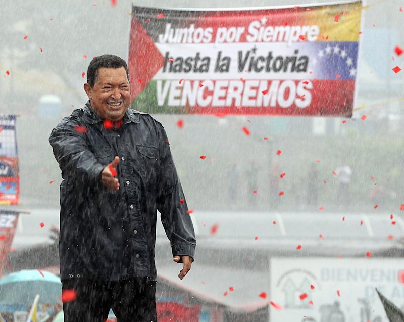 During a heavy rainstorm, Venezuelan President Hugo Chavez greets supporters at a campaign rally in Caracas, Venezuela on Thursday, October 4, 2012. (Pedro Portal/El Nuevo Herald/Tribune News Service via Getty Images)