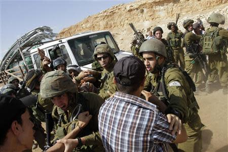 Israeli soldiers scuffle with Palestinians near a truck loaded with items European diplomats wanted to deliver to locals in the West Bank herding community of Khirbet al-Makhul, in the Jordan Valley September 20, 2013. REUTERS/Abed Omar Qusini