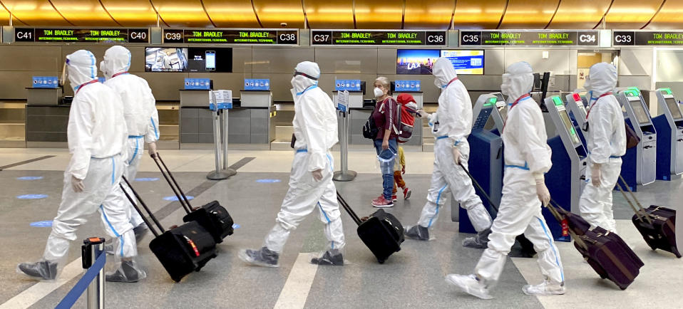 A woman, accompanied by a child, looks over as an airline crew wearing full personal protective equipment against COVID-19 walks through the international terminal at Los Angeles International Airport in Los Angeles on Tuesday, Nov. 17, 2020. (Keith Birmingham/The Orange County Register via AP)