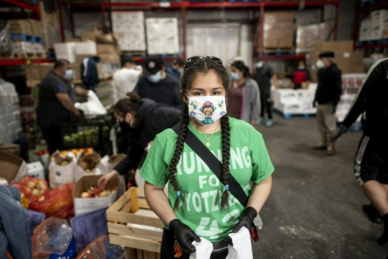 Student Heidy Animas helps prepare food parcels for Latin American members of a Lutheran church hit hard by the COVID-19 epidemic (AFP Photo/Johannes EISELE)