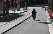 A man rides a scooter by an almost empty street during a workday following the implementation of stricter social-distancing and self-isolation rules to limit the spread of the coronavirus disease (COVID-19) in Sydney