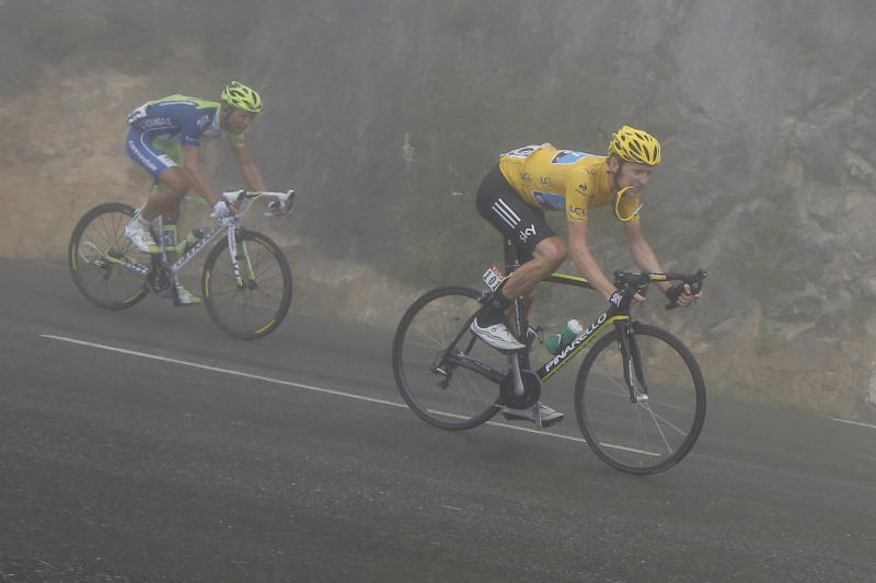 Bradley Wiggins of Britain, wearing the overall leader's yellow jersey, holds his glasses between his teeth as he speeds down Mente pass with Kristian Koren of Slovenia in dense fog during the 17th stage of the Tour de France cycling race over 143.5 kilometers (89.2 miles) with start in Bagneres-de-Luchon and finish in Peyragudes, Pyrenees region, France, Thursday July 19, 2012. (AP Photo/Laurent Cipriani)