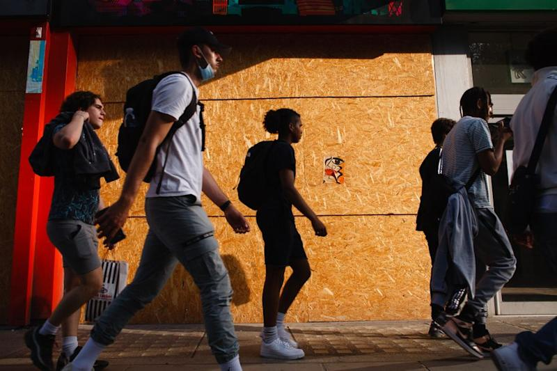 Young men walk past a boarded-up retail unit on Oxford Street in London.