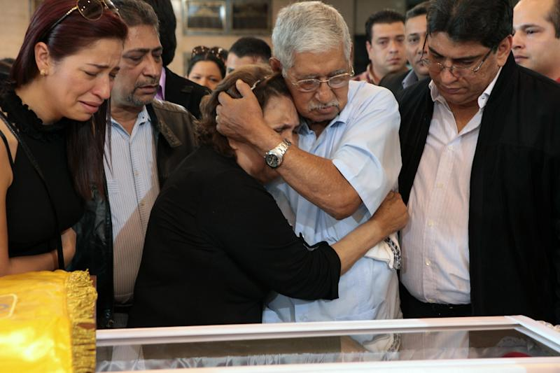 In this photo released by Miraflores Press Office, Hugo Chavez' s father Hugo de los Reyes Chavez, center right, comforts his wife Elena Frias as they stand next to the coffin containing the body of Venezuela's late President Hugo Chavez on display during his wake at a military academy where his body will lie in state until his funeral in Caracas, Venezuela, Thursday, March 7, 2013. Nicolas Maduro, Venezuela's acting president, said Chavez's remains will be put on permanent display at the Museum of the Revolution, close to the presidential palace where Chavez ruled for 14 years. A state funeral for Chavez attended by some 33 heads of government is scheduled to begin Friday morning. (AP Photo/Miraflores Press Office)