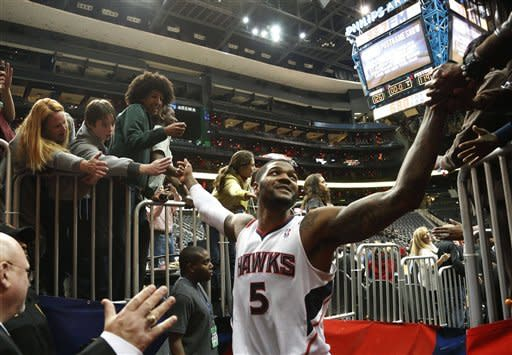 Atlanta Hawks small forward Josh Smith (5) celebrates with fans as he leaves the court after an NBA basketball game against the Detroit Pistons, Wednesday, Dec. 26, 2012, in Atlanta,. Atlanta won 126-119 in double overtime. (AP Photo/John Bazemore)