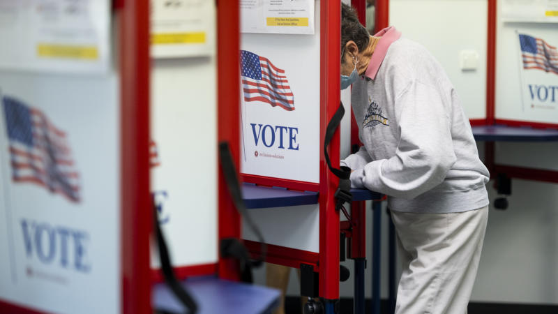 A voter fills out her ballot