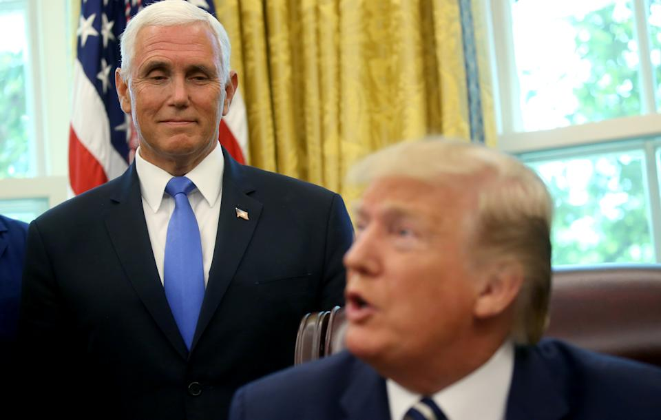 ?Vice President Mike Pence? watches U.S. President Donald Trump as Trump acknowledges former astronauts and their family members during an Apollo 11 moon landing 50th anniversary commemoration in the Oval Office of the White House in Washington, U.S., July 19, 2019. REUTERS/Leah Millis