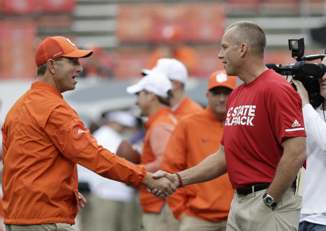 FILE - In this Nov. 4, 2017, file photo, Clemson head coach Dabo Swinney, left, and North Carolina State head coach Dave Doeren shake hands before an NCAA college football game in Raleigh, N.C. The Atlantic Coast Conference has yet to have a big game this season, and might not have another one after Saturday until its conference championship game. No. 16 North Carolina State visits No. 3 Clemson in matchup of the only remaining unbeaten teams in the ACC. (AP Photo/Gerry Broome, File)
