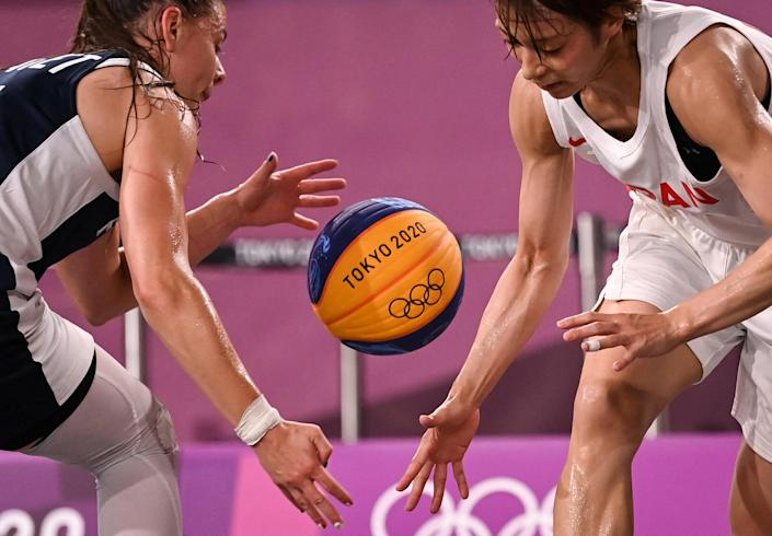 <p>France's Marie-Eve Paget (left) fights for the ball against Japan's Mio Shinozaki during the women's quarterfinal 3x3 basketball match between Japan and France.</p>