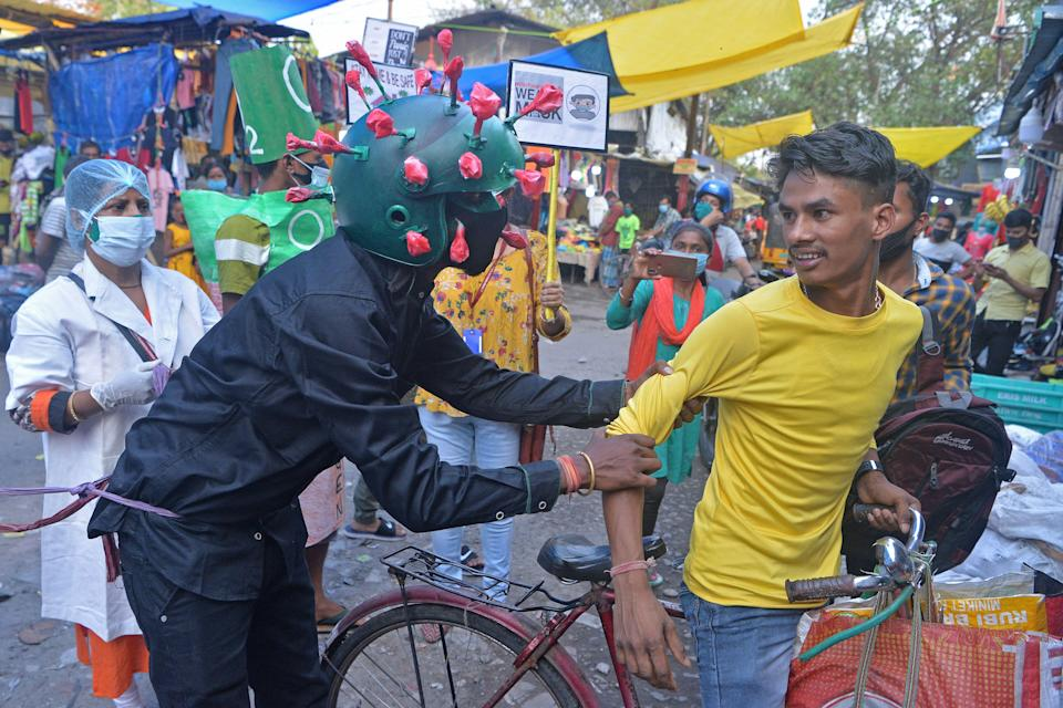 <p>A man from a non-governmental organisation, wearing an outfit resembling the coronavirus, urges people to follow safety protocols in Siliguri on 25 April, 2021</p> (AFP via Getty Images)