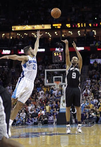 San Antonio Spurs point guard Tony Parker (9) hits a three-pointer over New Orleans Hornets point guard Greivis Vasquez (21) with 51 second remaining in the game to punt the Spurs ahead for good in the second half of an NBA basketball game in New Orleans, Wednesday, Oct. 31, 2012. The Spurs won 95-99. (AP Photo/Gerald Herbert)