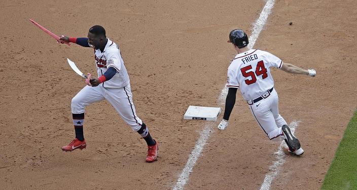 Atlanta Braves' Max Fried (54) rounds first base after making the winning hit against the Miami Marlins as Guillermo Heredia, left, storms the field during the 10th inning of a baseball game Sunday, July 4, 2021, in Atlanta. (AP Photo/Ben Margot)