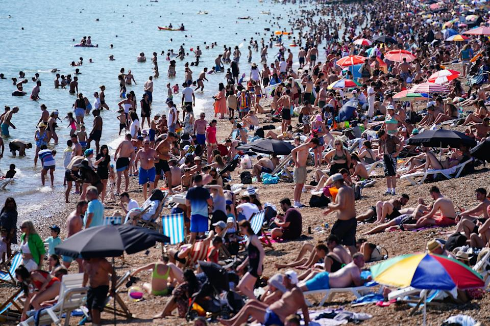 People enjoy the hot weather on Brighton beach in East Sussex (Victoria Jones/PA) (PA Wire)