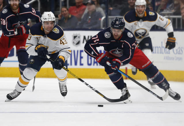 Columbus Blue Jackets forward Nick Foligno, right, chases the puck against Buffalo Sabres forward Conor Sheary during the second period of an NHL hockey game in Columbus, Ohio, Monday, Oct. 7, 2019. (AP Photo/Paul Vernon)