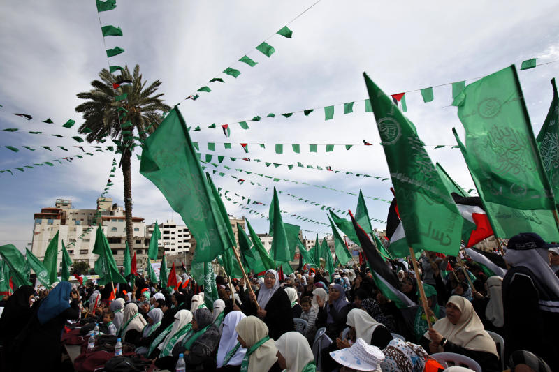 Palestinian women wave green Islamic and national flags during a support rally for Palestinian prisoners who are held at Israeli jails, in Gaza City, Thursday, April 11, 2013. Nearly 5,000 Palestinians are being held in Israeli prisons according to prisons authority spokeswoman Sivan Weizman. (AP Photo/Adel Hana)