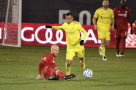 Nashville SC's Randall Leal, right front, trips over the foot of Toronto FC's Michael Bradley during the first half of an MLS soccer playoff match Tuesday, Nov. 24, 2020, in East Hartford, Conn. (AP Photo/Jessica Hill)