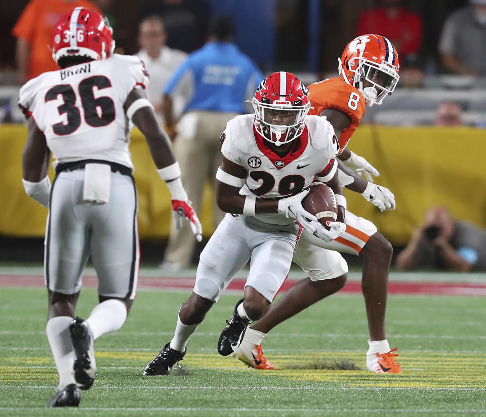 Georgia defensive back Christopher Smith intercepts a pass intended for Clemson wide reciever Justyn Ross, right, and goes on to score a touchdown during the second quarter of an NCAA college football game Saturday, Sept. 4, 2021, in Charlotte, N.C. (Curtis Compton/Atlanta Journal-Constitution via AP)