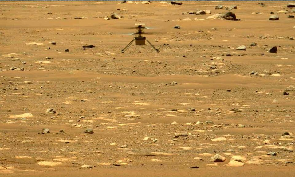 In this image made available by NASA, the Mars Ingenuity helicopter hovers above the surface of the planet.