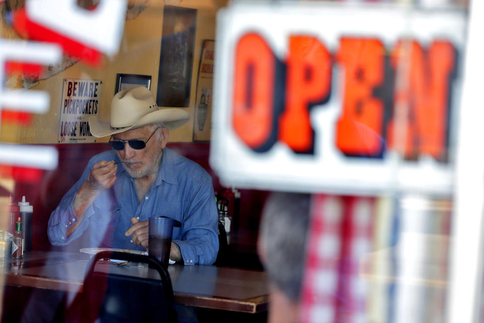 A customer eats inside the Horseshoe Cafe Friday, May 1, 2020, in Wickenburg, Ariz. A few small businesses reopened in defiance of Arizona Gov. Doug Ducey's decision to extend a statewide stay-at-home order for another two weeks. (AP Photo/Matt York)