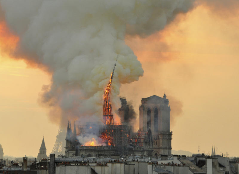 "In this image made available on Tuesday April 16, 2019 flames and smoke rise from the blaze as the spire starts to topple on Notre Dame cathedral in Paris, Monday, April 15, 2019. An inferno that raged through Notre Dame Cathedral for more than 12 hours destroyed its spire and its roof but spared its twin medieval bell towers, and a frantic rescue effort saved the monument's ""most precious treasures,"" including the Crown of Thorns purportedly worn by Jesus, officials said Tuesday. (AP Photo/Thierry Mallet)"