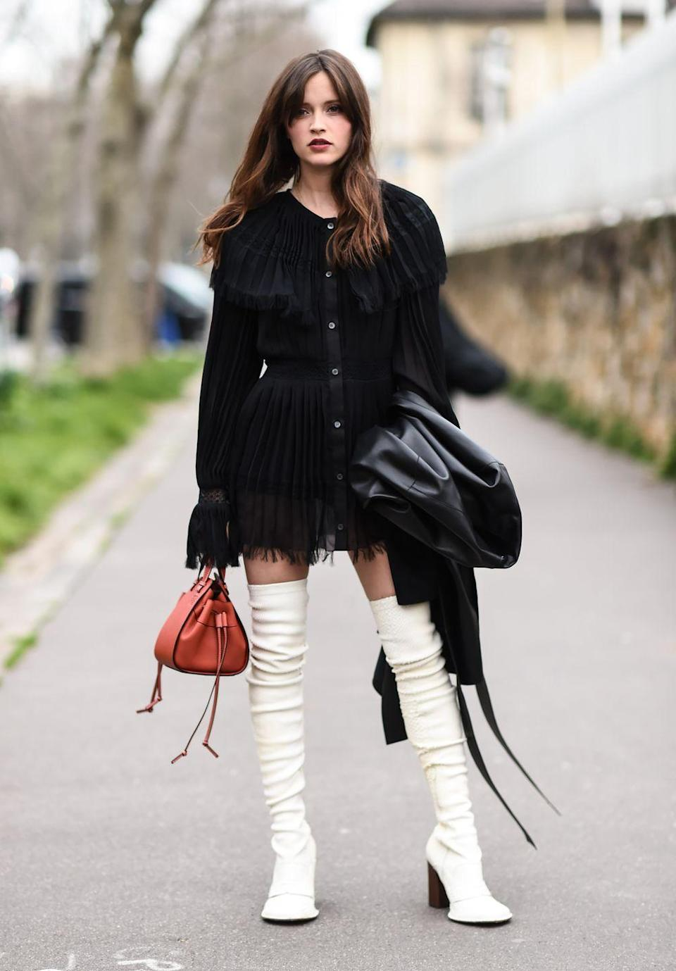 <p>Cream boots and a red-orange bag add some color to a black ruffled mini</p>
