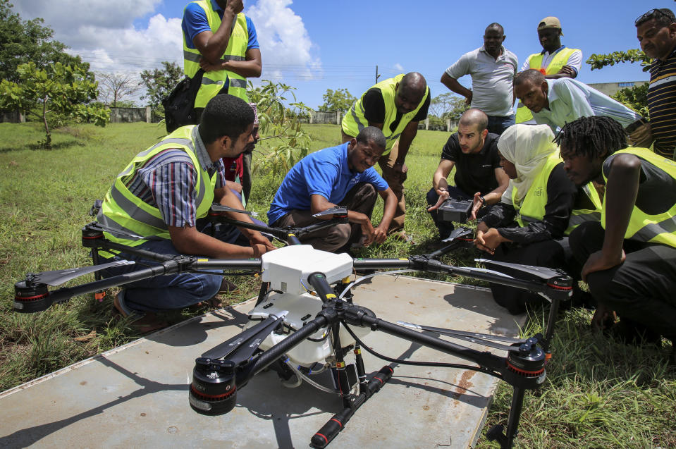 In this photo taken Thursday, Oct. 31, 2019, Eduardo Rodriguez, center-right, of drone manufacturer DJI, shows trainee drone pilots from the State University of Zanzibar how to fly a drone to spray the breeding grounds of malaria-carrying mosquitoes, at Cheju paddy farms in the southern Cheju region of the island of Zanzibar, Tanzania. Drones spraying a silicone-based liquid that spreads across the large expanses of stagnant water where malaria-carrying mosquitoes lay their eggs, are being tested to help fight the disease on the island of Zanzibar, off the coast of Tanzania. (AP Photo/Haroub Hussein)