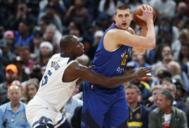 Minnesota Timberwolves center Gorgui Dieng, left, defends against Denver Nuggets center Nikola Jokic who looks to move to the rim in the first half of an NBA basketball game Friday, Dec. 20, 2019, in Denver. (AP Photo/David Zalubowski)