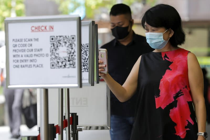 Office workers scan a Safe Entry QR code to enter a mall, amid the coronavirus disease (COVID-19) outbreak in Singapore