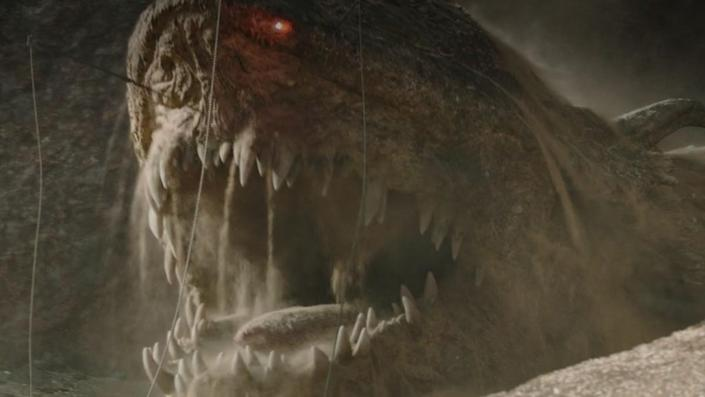 The giant krayt dragon pops from his pit in a scene from The Mandalorian.